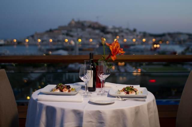 cena romántica inolvidable terraza mesa servida copas botella vino aniversario